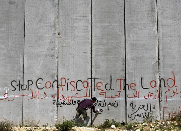 Palestinian protester spray paints on controversial Israeli barrier near Bethlehem